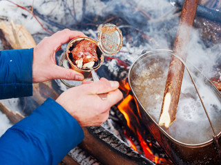 Cooking soup on a fire pot. Tourist puts stewed meat in soup from tin can. Winter camping in forest.