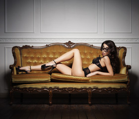 Sexy and beautiful woman in erotic lingerie on a sofa. Fashion, vogue, glamour concept.