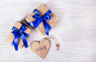Two gift boxes with blue ribbons and a heart from a tree on a white wooden background. Valentine's day. Copy space.