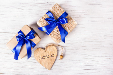 """Two gift boxes with blue ribbons and wooden heart on a white background. The inscription inside the heart """"I Love"""" Valentine's Day. Copy space."""
