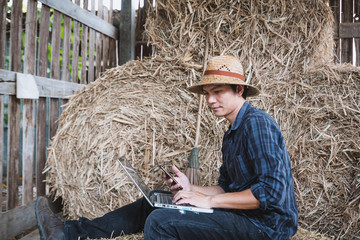 Farmer family with laptop in hay shed.