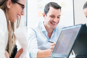 Team in Büro bei Meeting, Fokus auf Geschäftsmann bei Arbeit