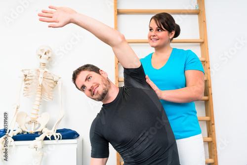 junger mann macht bungen auf pezziball mit physiotherapeutin stockfotos und lizenzfreie. Black Bedroom Furniture Sets. Home Design Ideas