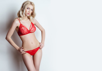 sexy blonde girl in red lace lingerie posing in the studio on a red background. Advertising Space