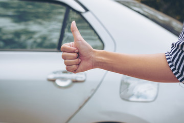 Hand thumb up with the car  background.