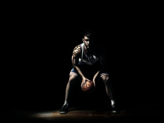 basketball player in durkness on parquet with ball