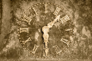 Vintage rusty clock in front of a stone background