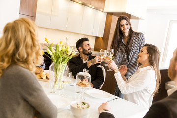 Friends having a meal at dining table and toast with  white wine