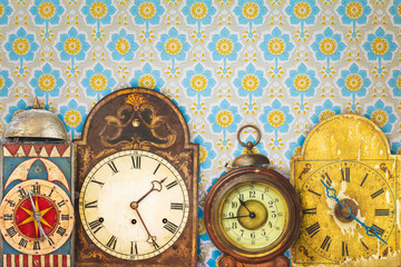Colorful vintage clocks in front of retro wallpaper