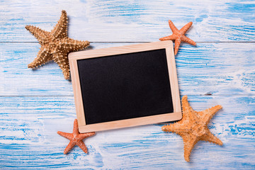 Tropical frame with starfishes on blue wooden background