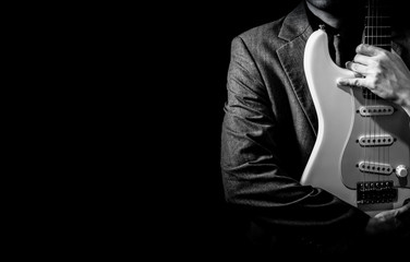 BW male musician in suit posing on white electric guitar, isolated on black