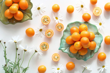 Fresh kumquat and marguerite flower on white background