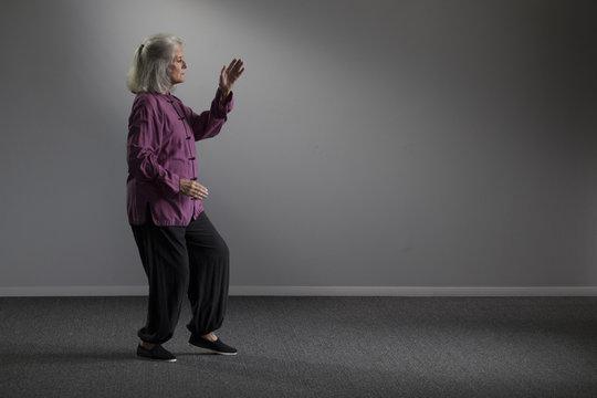 A senior woman doing tai chi