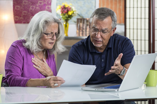 A senior aged couple looking at their bills