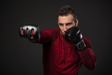 Young man looking aggressive with boxing gloves.