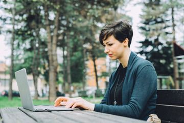 Young beautiful caucasian brown hair woman sitting on a bench in a park using computer and smart phone – technology, multitasking, business concept