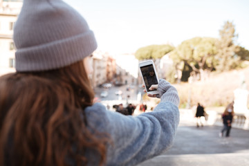 Woman taking pictures with blank screen mobile phone in city