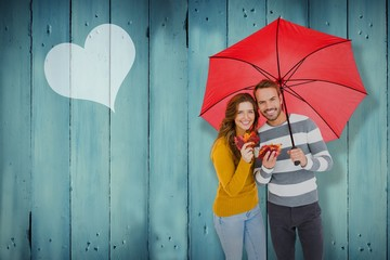Composite image of happy young couple holding umbrella