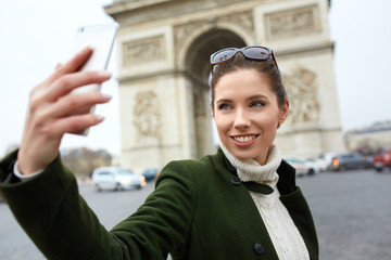 young woman visiting Paris. Triumphal arch. make selfie