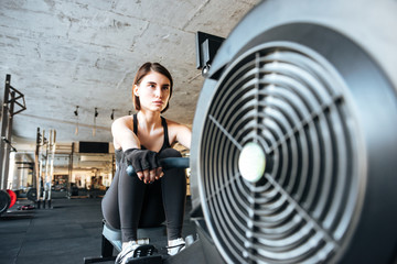 Woman athlete working out with training machine in gym