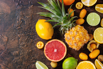 Variety of whole and sliced citrus fruits pineapple, grapefruit, lemon, lime, kumquat, clementine and physalis over dark textured background. Top view with space. Healthy eating, dieting