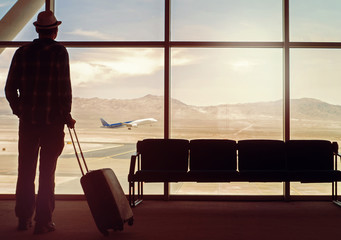 Silhouette of travelling man in the airport holding a suitcase a