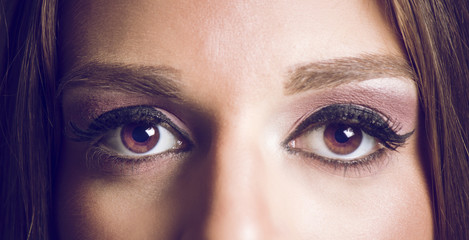 Close-up of a woman's eyes. Focus on eye retina. Beautiful brown eyes close up photo.
