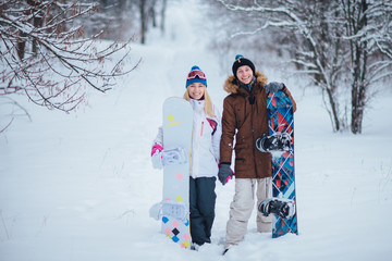 two happy snowboarders in winter forest
