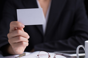 A business woman in black suit holding a white blank business cardname card