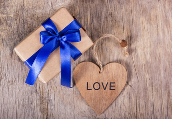 Gift on Valentine's Day. Gift box with a blue bow and a wooden heart. Copy space. Valentine's day.