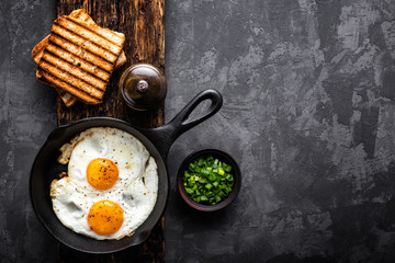 fried eggs on dark background with space for text
