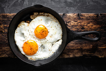 Photo on textile frame Egg fried eggs in black pan