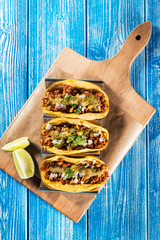Mexican tacos campechanos top view on a blue wooden table.