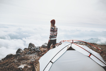 Traveler on mountains summit over clouds Travel Lifestyle concept adventure vacations outdoor tent camping