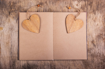 Notepad with blank pages and bookmarks in the shape of a heart. Wooden valentine. Valentine's Day. Copy space