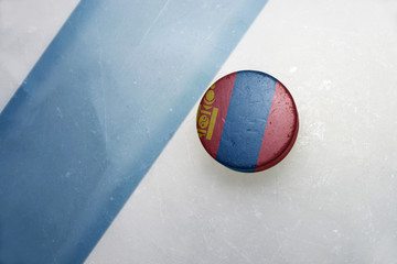 old hockey puck with the national flag of mongolia.