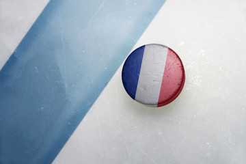 old hockey puck with the national flag of france.