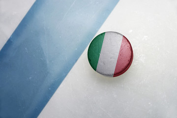 old hockey puck with the national flag of italy.