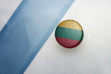 old hockey puck with the national flag of lithuania.