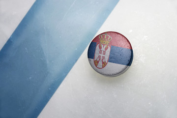 old hockey puck with the national flag of serbia.