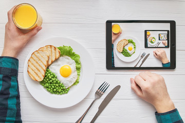 Healthy morning breakfast online browsing concept with tablet screen endless picture design. Man's hands with fried eggs, peas, bread and juice vegetarian diet meal. Digital internet home lifestyle