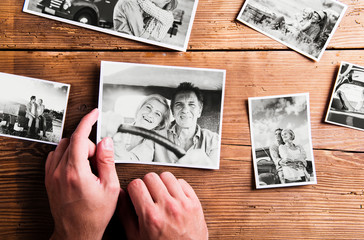 Hands holding pictures of senior couple. Studio shot, wooden bac