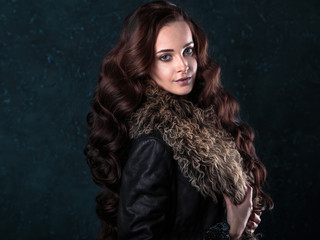 Young brunette woman with perfect natural makeup and hair style wearing furs. fashion beauty portrait
