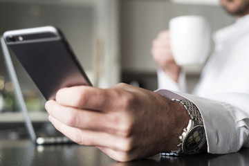 Business professional checking phone while drinking coffee