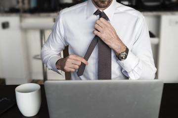 Businessman tying his tie at desk