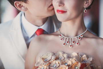 Portrait of wedding couple, close-up of bride with red lips and luxury jewelry and groom with red tie