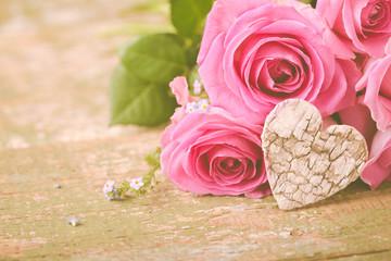 Rosen und Herz auf altem Holztisch