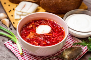Borsch - traditional Ukrainian and Russian soup with red beets in ceramic bowl on wooden background
