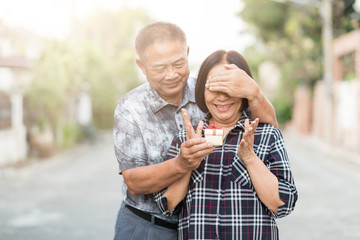 Happy Senior Asian man covering eyes of senior Asian woman for surprise with gift box.