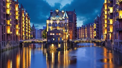 Fototapete - House and two brides in the evening in Speicherstadt district, Hamburg, Germany  (static image with animated sky and water)